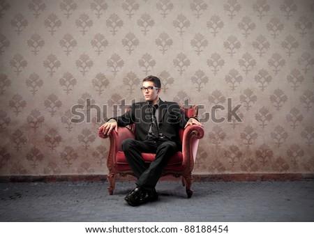 Businessman sitting on a velvet armchair