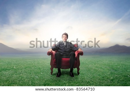 Businessman sitting on an armchair on a green meadow