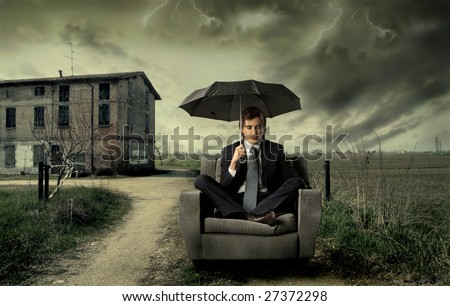 businessman sitting on armchair with umbrella in the countryside