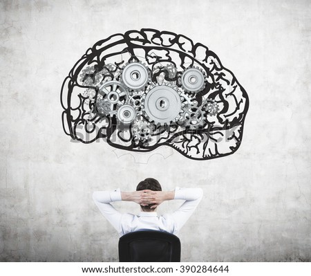 Businessman sitting on chair with hands on head and looking at image of brain with gears on concrete wall. Back view. Concept of mental work. #390284644
