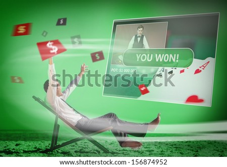 Businessman sitting on deck chair looking at holographic screen in green light on the beach