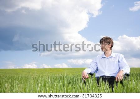 Businessman sitting on green grassland under blue sky