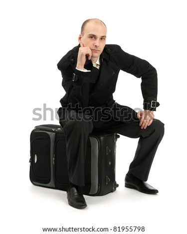 businessman sitting on his luggage isolated on white