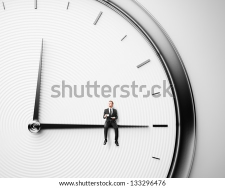 Businessman sitting on minute hand with cup of coffee