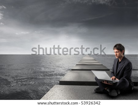 Businessman sitting on pads over the sea and using a laptop