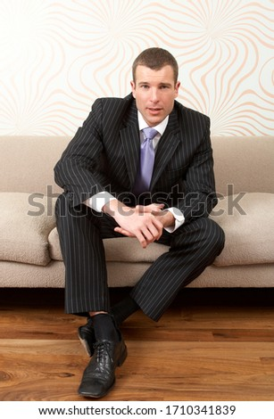 Businessman sitting on sofa in his suit