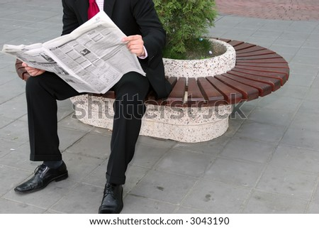 Businessman sitting on the bench and reading newspapers