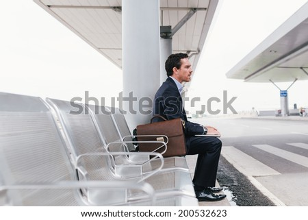 Businessman sitting on the chair at the airport bus stop and looking away side view