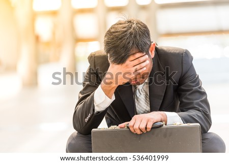 Businessman sitting on the floor near business centre at big city. He feel sad worry tired frustrated upset fail after lost work job from office . A man become unhappy and depressed person.
