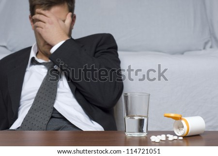 Businessman sitting on the floor. On the table glass of water and pills.