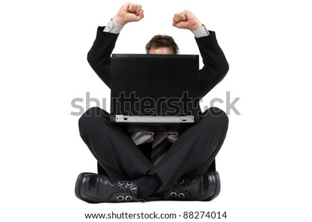 Businessman sitting on the floor with legs crossed celebrating news of success on his laptop