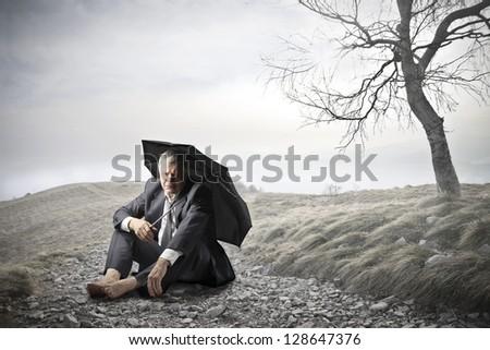 businessman sitting on the ground with umbrella