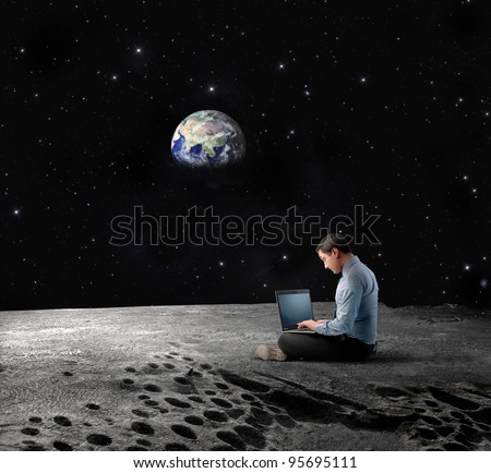 Businessman sitting on the Moon and using a laptop with Earth in the background \
