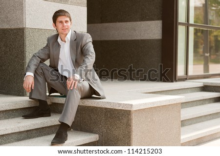 Businessman sitting on the steps of the horizontal frame