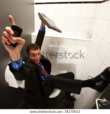 businessman sitting on toilet with hands up