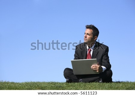 Businessman sitting outdoors with laptop computer - stock photo