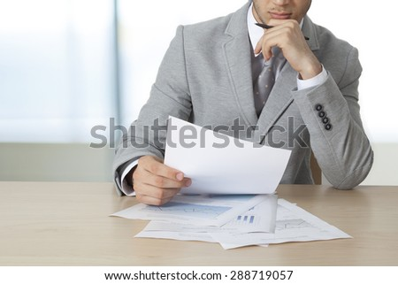 Businessman sitting table and holding document