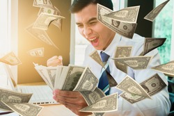 Businessman sitting watching the dollar in the office, Businessman happy with dollars in hand, Business success concept - Image