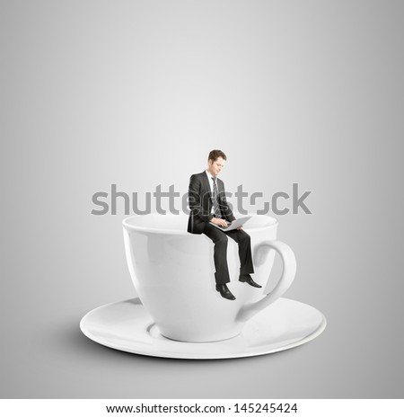 businessman sitting with laptop on cup