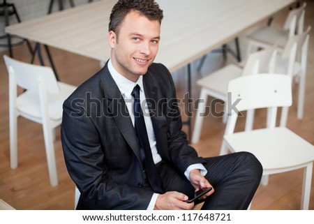 Businessman sitting with smartphone