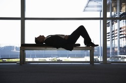 Businessman sleeping on bench in office building