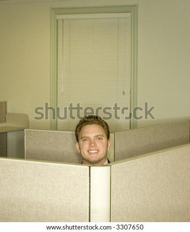 Businessman smiles and shows his head above the office cubicles