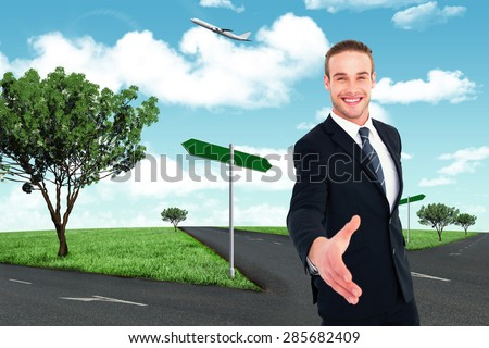 Businessman smiling and offering his hand against road leading out to the horizon