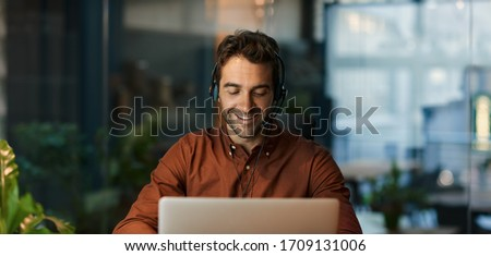 Businessman smiling and talking with a client over a headset while working alone at his desk in a dark office after hours Stock fotó ©