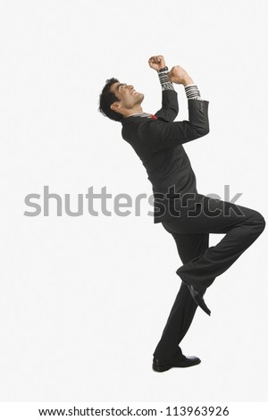 Businessman smiling with his arms raised