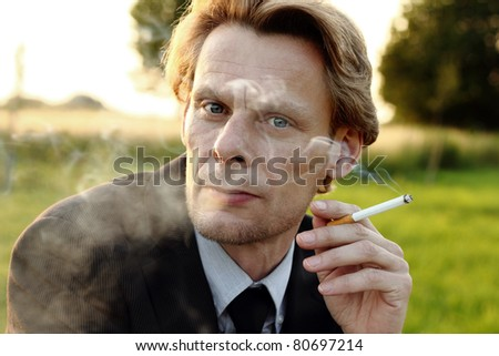 Businessman smoking a cigarette outdoors with field on background, looking relaxed - stock photo