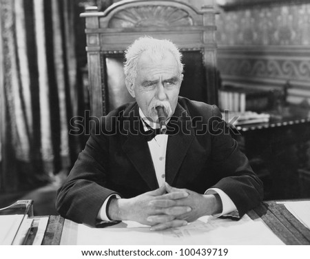 Businessman smoking cigar at desk