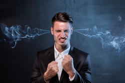 Businessman smoking from ears with anger