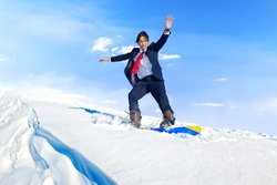 Businessman snowboarding on top of a mountain.