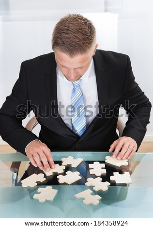 Businessman solving a jigsaw puzzle at his desk sitting down with the pieces spread out in front of him  conceptual of problem solving and challenges and work