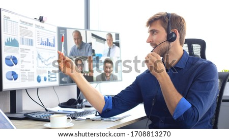 Businessman speak talk on video call with colleagues on online briefing during self isolation and quarantine. Webcam group conference with coworkers on laptop at office. Flu epidemic and covid-19.