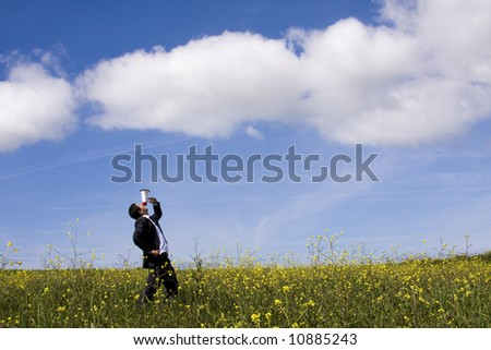 Businessman speaking with a megaphone in a field