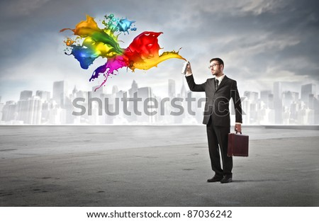 Businessman spraying colored paint with cityscape in the background