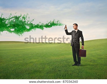 Businessman spraying green paint on a green meadow