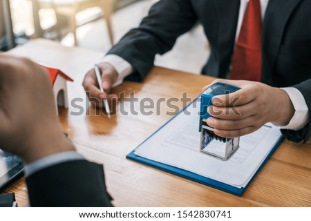 Businessman stamping with approved stamp on document contract. #1542830741
