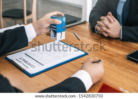 Businessman stamping with approved stamp on document contract. #1542830750