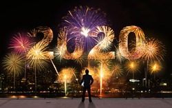 businessman stand on roof top of skyscrabber watching fireworks business success conceptual image for the year 2020