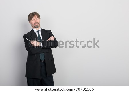 Businessman standing against a blank gray wall.