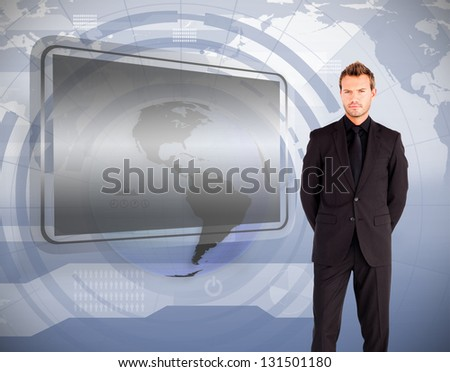 Businessman standing against blank screen and interface in blue and grey
