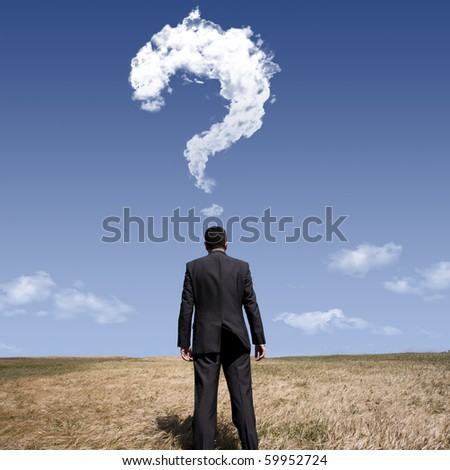 businessman standing alone at the field with a lot of questions in his mind - stock photo