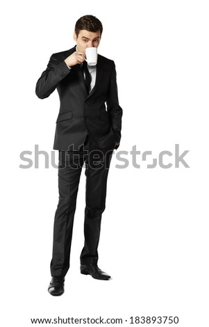 Businessman standing and drinking coffee against white background.