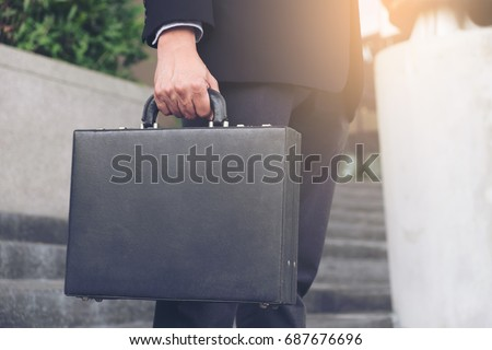Businessman standing and holding a briefcase in hand working with confidence.