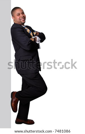 Businessman standing and leaning on wall isolated over a white background.