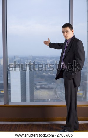 Businessman Standing and Looking at the Camera. There's Big Window With Big City View Behind Him. - stock photo