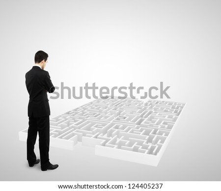 businessman standing and looking to white labyrinth
