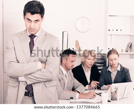 Businessman standing apart feeling angry to coworkers in office